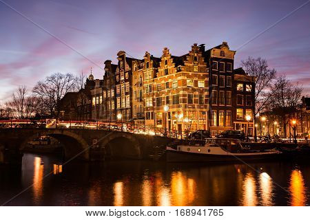 Amsterdam canal houses in traditional style next to a bridge over Prinsengracht en Brouwersgracht canals illuminated at dusk during Blue Hour in the Netherlands.