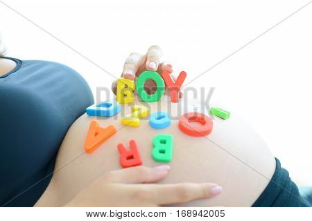 Young expectant mother with letter blocks spelling boy on her pregnant belly