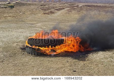 burning tire at tactical field in spring