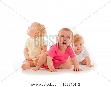 Three crying blondes babies, sitting isolated on white