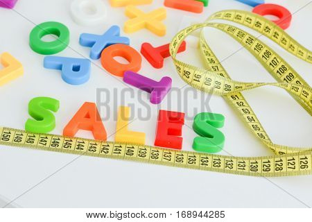 Measurement of sales concept on white background with colorful magnetic letters and measuring tape