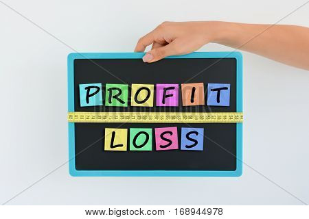 Measure your profit versus loss concept written as magnetic colored letter blocks with scale