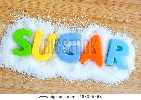 Sugar text from magnetic letters concept on wooden background
