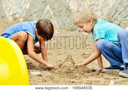 two funny boys playing sand in summer time