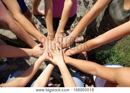Group of young people putting their hands on top of each other