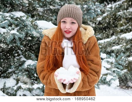 beautiful woman play with snow on winter outdoor, snowy fir trees in forest, long red hair, wearing a sheepskin coat