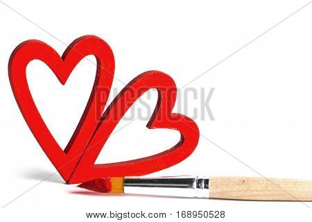 Two wooden red painted Valentine day hearts and paint brush isolated on white background