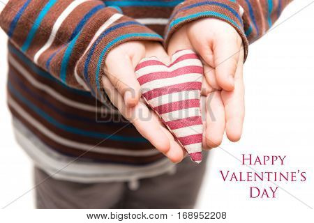 Striped heart in hands of little kid. Isolated on a white background with text: Happy Valentine's Day
