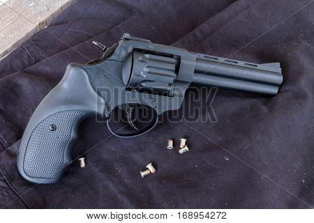 Revolver Flaubert on a dark background with bullets.