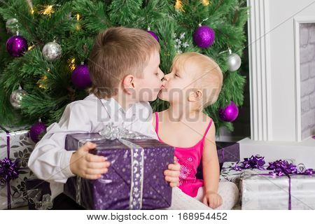 Children exchange gifts and kiss under the festive fir in New Year