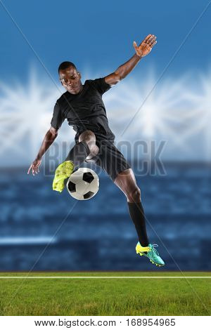 African American soccer player kicking ball inside stadium