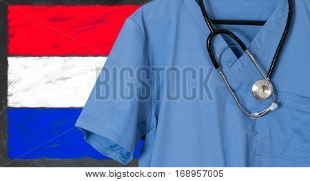 Blue doctor scrubs shirt and stethoscope hang empty in front of Luxembourg flag. Illustration of medical staff coming from other countries to staff health systems