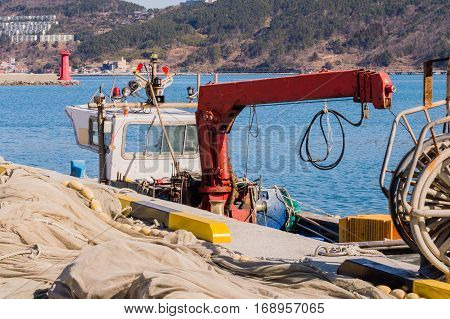 Boat with a large red hydraulic arm docked at a pier covered with fishing net with the ocean and a small coastal community in the background