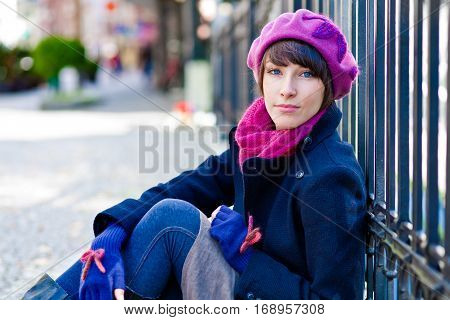 fashionable young woman wearing pink beret scarf and blue gloves