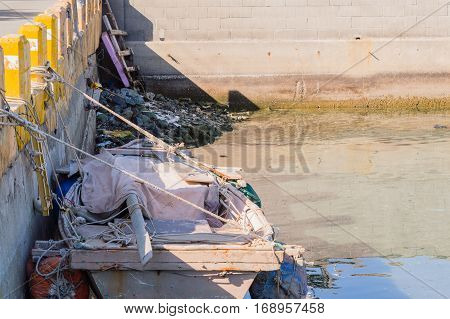 Wooden rowboat dry docked and tied to concrete pillars with garbage and debris in the background