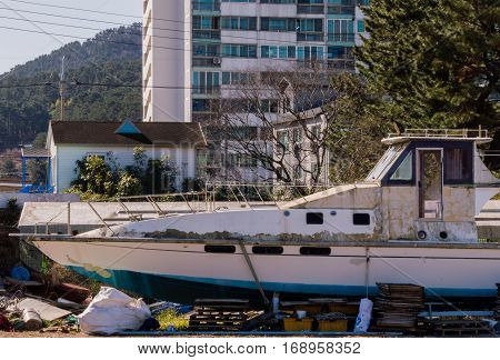 Large boat in a state of disrepair in dry dock with buildings and trees in the background