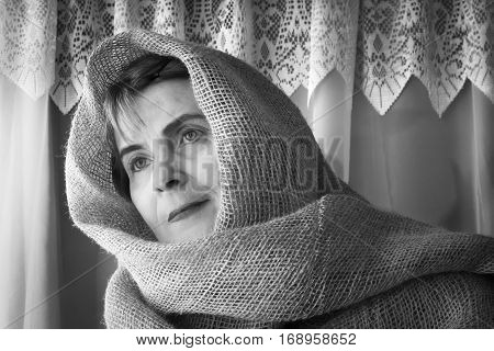 horizontal black and white head shot of a woman wearing a burlap head covering wrapped loosely around the head and shoulder.