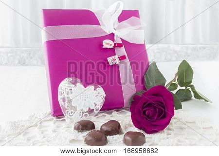 horizontal image of a pink paper wrapped gift with white ribbon and a rose lying beside and some chocolates in heart shape for valentines day on white background.