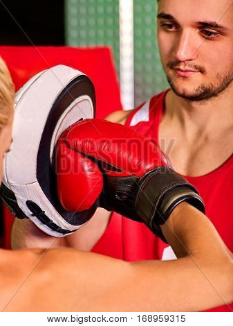 Boxing workout woman in fitness class. Sport box exercise two people. Man trainer holding sport mitts in gym. Female boxing gloves are red.