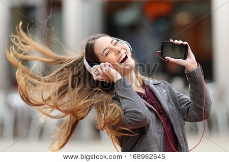 Excited girl dancing and listening music with headphones and smart phone in the street with hair moving