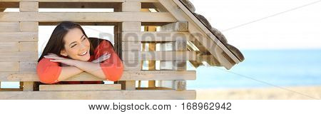 Front panoramic view of a woman thinking in the new apartment of her dreams looking through a window of a toy house on the beach