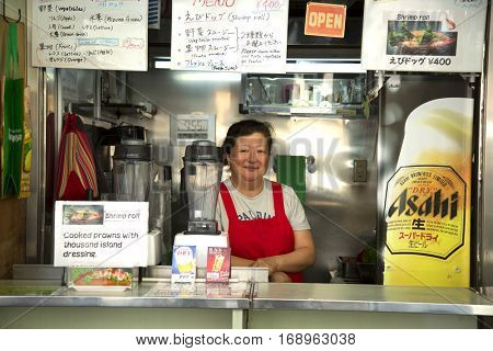 TOKYO-JAPAN, 27 June 2016: Smiling and proud japanese woman standing in her restaurant at tsukiji fish market in Tokyo, japan. The biggest wholesale fish and seafood market in the world.