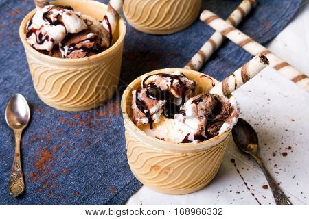 Delicious ice cream in a cup with chocolate sauce and cream rolls