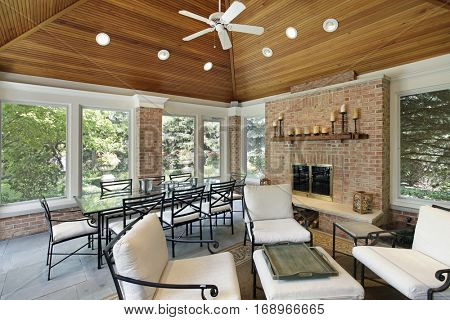 Porch in luxury home with brick fireplace.