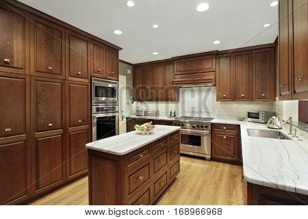 Kitchen in luxury home with wooden drawers on granite-top counter.
