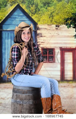 A beautiful young teenage cowgirl holding a rope while sitting on an old barrel in a wild-west town.