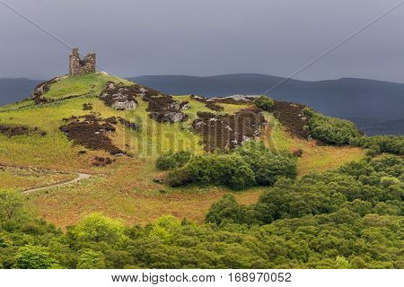 North Coast, Scotland - June 6, 2012: On a bright green hilltop stand the remains of a castle tower near the village of Tongue under a dark gray sky. Foreground is the hill with many hues of green and brown.
