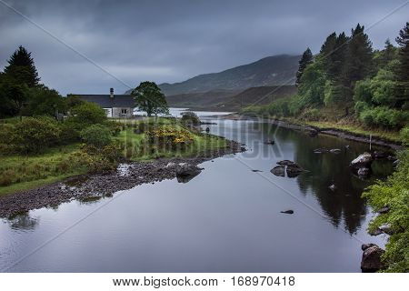 North Coast, Scotland - June 6, 2012: The shallow bluish gray reflecting Hope River meanders through a green landscape in front of tall mountains. Shades of green and yellow accents by broom flowers. Half hidden house.