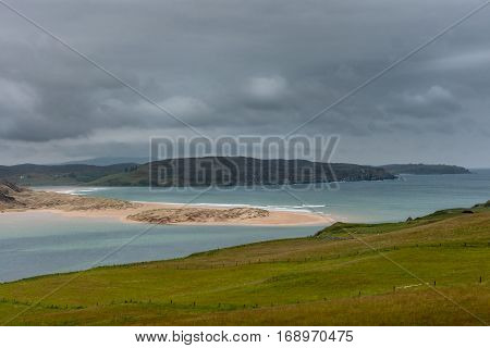 North Coast, Scotland - June 6, 2012: large sandbank blocks partly the mouth of Naver River under gray cloudy sky. Azure blue water green foreground mountainous background.