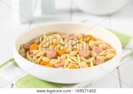 Chilean traditional Porotos con Riendas (beans with reins) dish of cooked dried beans with pumpkin onion spaghetti and sausage photographed on white wood with natural light (Selective Focus Focus one third into the dish)
