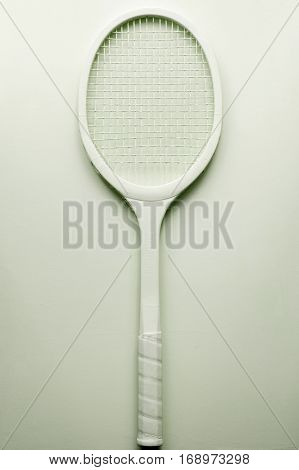 Green tennis racket on green table. Handmade vintage sport accessory minimalism fine art
