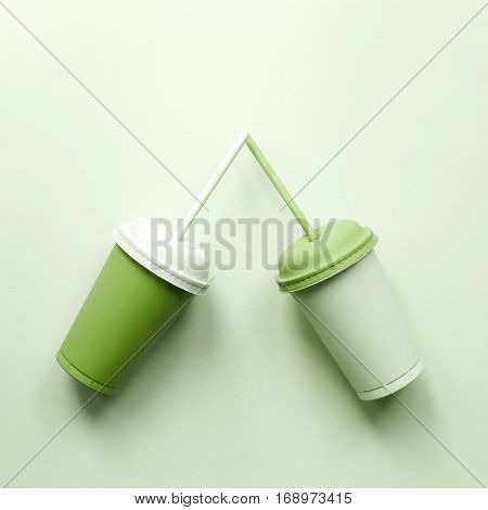 Two plastic cups on green. Greenery art drink poster. Cola, water or juice
