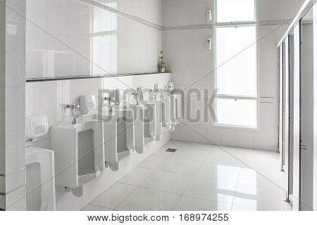 White Urinals In Clean Men Public Toilet Room Empty.