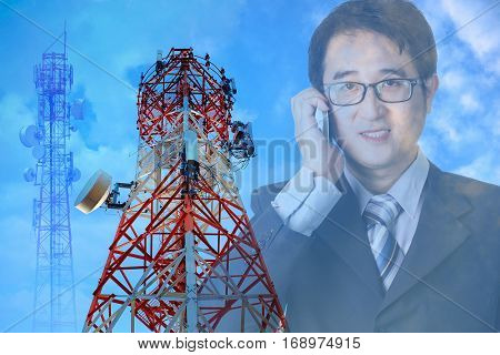 Telecommunication towers foreground on Asian businessman using mobile phone background over exposure.