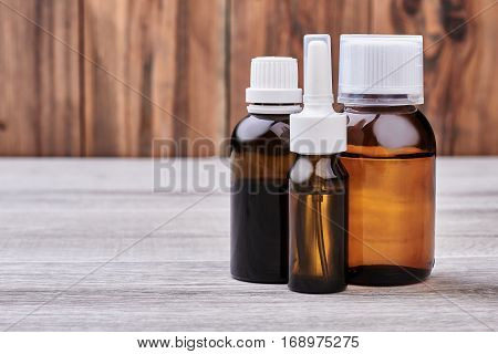 Medicine bottles on wooden background. Nasal spray container. Strengthen your immune system.