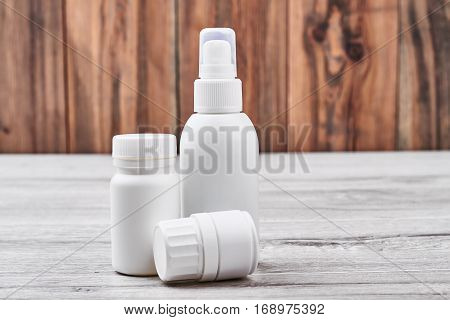 Medicine containers on wooden backdrop. Plastic pill boxes.
