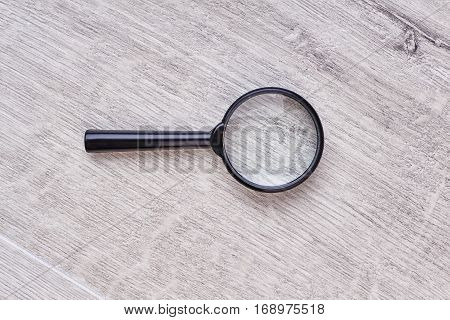 Magnifying glass on wooden backdrop. Top view of loupe. How to become a scientist.