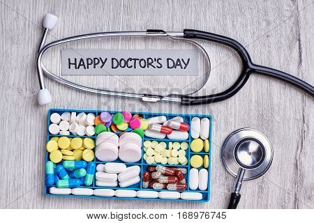 Drugs in organizer and stethoscope. Medical tools on wooden background. Happy doctor's day to you.