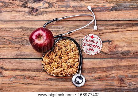 Apple, greeting card and stethoscope. Walnuts in a box. Congratulation for a cardiologist.