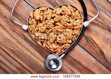 Heart-shaped box with walnuts. Stethoscope on wooden backdrop. My profession is a doctor.