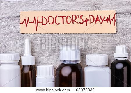 Paper card and medical bottles. Professional holiday of cardiologist.