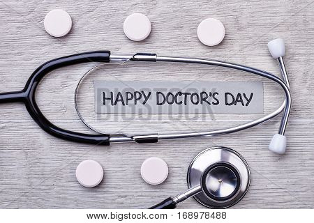 Stethoscope, tablets and card. International Doctor's Day Greeting.