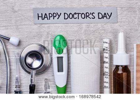 Thermometer, bandage and greeting card. Happy and joyful Doctor's Day.