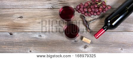 Flat view of a bottle of red wine antique corkscrew grapes and drinking glasses on rustic wooden boards