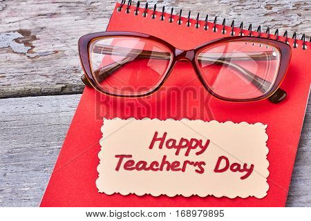 Glasses, notebook on wooden surface. Sincere greeting for dear teacher.