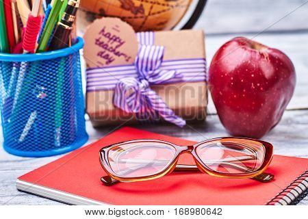 Basket with stationery and glasses. Apple, notebook and present box. Sincere wishes to teacher.